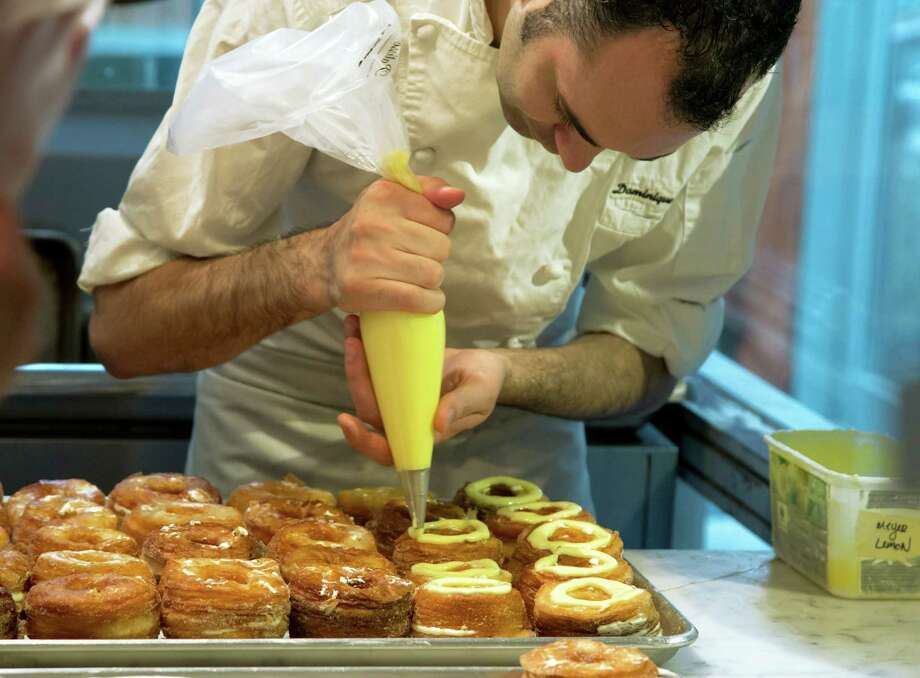 Chef Dominique Ansel makes Cronuts, a croissant-donut hybrid, at the Dominique Ansel Bakery in New York on June 3, 2013. The pastry chef introduced it in May 2013, and bakeries in London, Toronto, Seoul and elsewhere have copied it. (AP Photo/Richard Drew) Photo: Richard Drew / AP