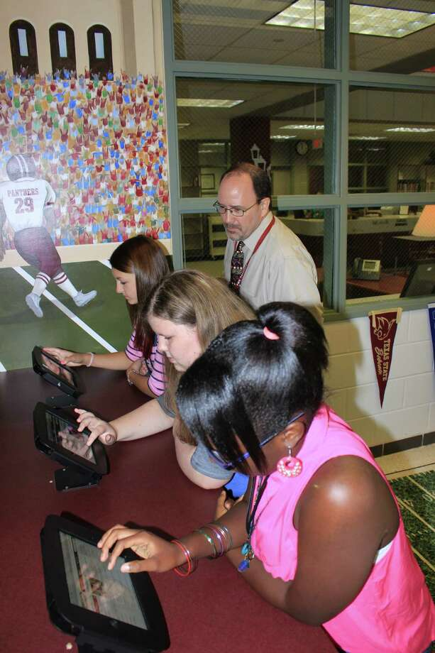 Principal Ken Buck assists 8th graders Akesia Watts, Erin McCarthy and Carly Wolosyn as they try out the new Career Corner technology. Photo: Courtesy