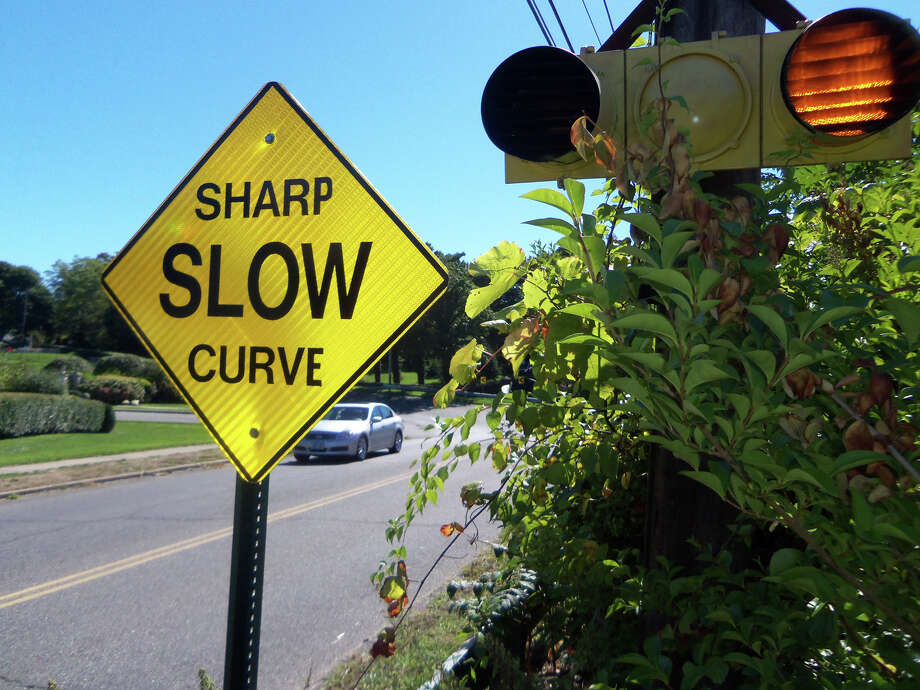 A sign warns motorists to slow for the dangerous curve ahead near the foot of Gulf Street in Milford, Conn., on Sept. 25, 2013. The city will start work soon on making the curve safer for both pedestrians and motorists. ItâÄôs been the scene of scores of accidents over the years. Photo: John Burgeson / Connecticut Post