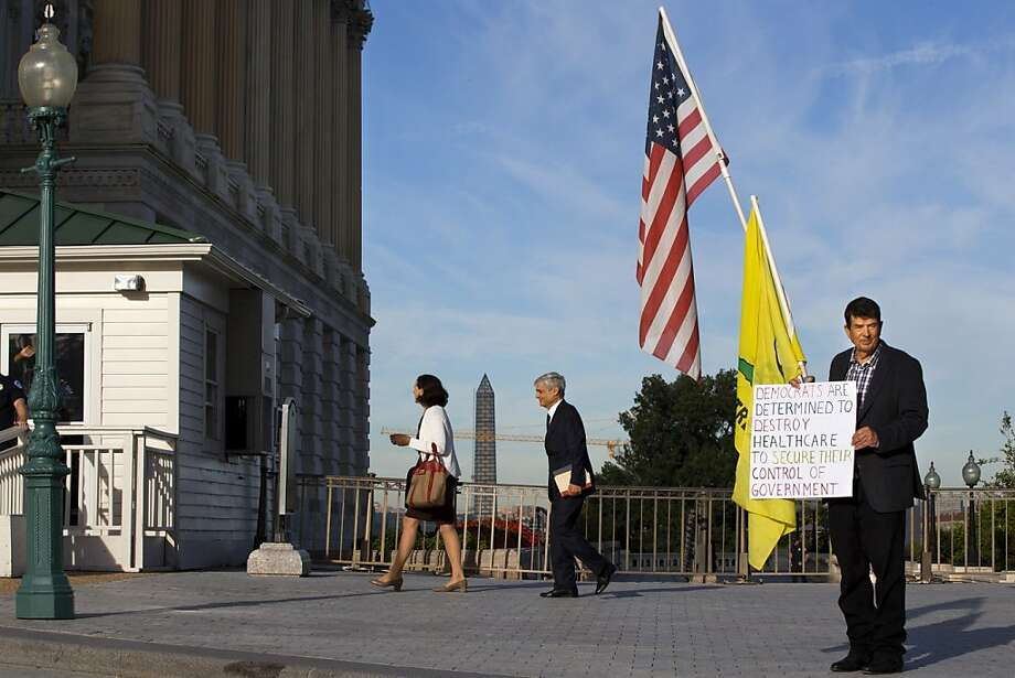 Former Treasury Secretary Robert Rubin (center) walks past Ron Kirby, a Tea Party member showing his stance against Obamacare outside the Capitol. Photo: Jacquelyn Martin, Associated Press