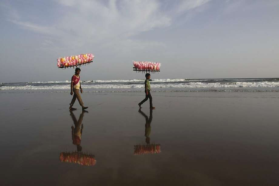 Got any saltwater taffy? Cotton candy vendors peddle their confection on the Bay of Bengal coast in Puri, 