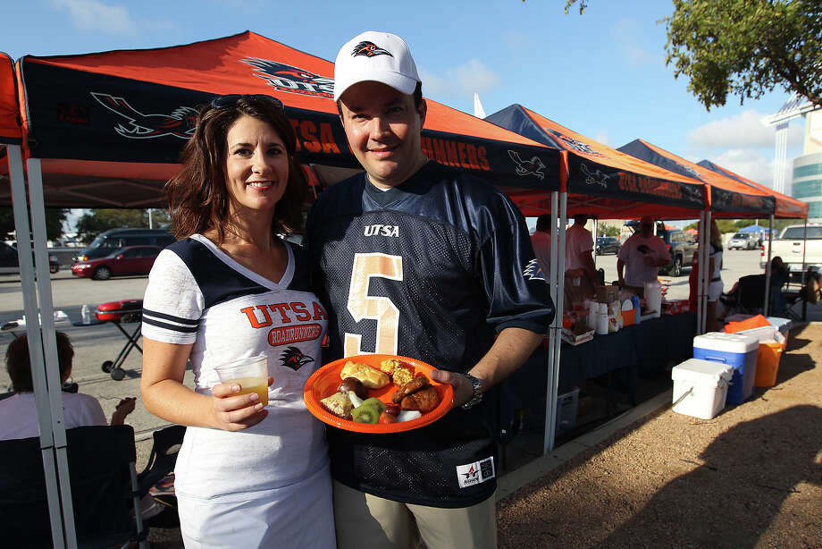 Jennifer and Marc Barrera have hosted tailgate parties before the UTSA football games since the inception of the university's program. They pick a spot, set up tents and with friends cook up a meal to enjoy before the UTSA game at the Alamodome on Saturday, Sept. 7, 2013. Photo: Kin Man Hui, San Antonio Express-News / ©2013 San Antonio Express-News