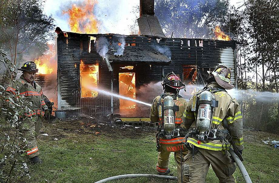 Volunteer firefighters battle a house fire in Morgantown, W.Va., in September. Such volunteers are considered employees, but small departments say they can't afford to provide health care. Photo: Bob Gay/The Dominion Post, Associated Press