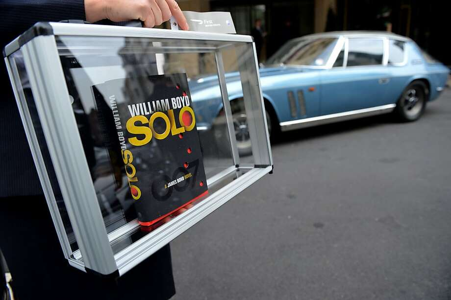 "007's cover revealed: British Airways ambassador Helena Flynn carries British author William Boyd's new James Bond novel ""Solo"" in a protective case a day ahead of the book's publishing in London. Photo: Leon Neal, AFP/Getty Images"