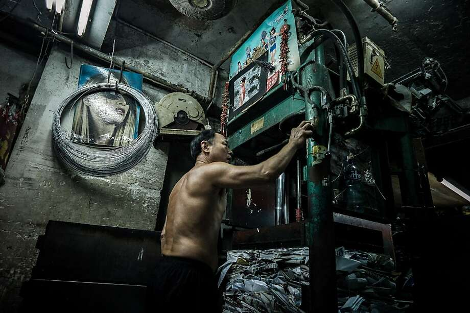 Press time: A worker activates an hydraulic press at a waste paper-collection outlet in Hong Kong. While the former British 