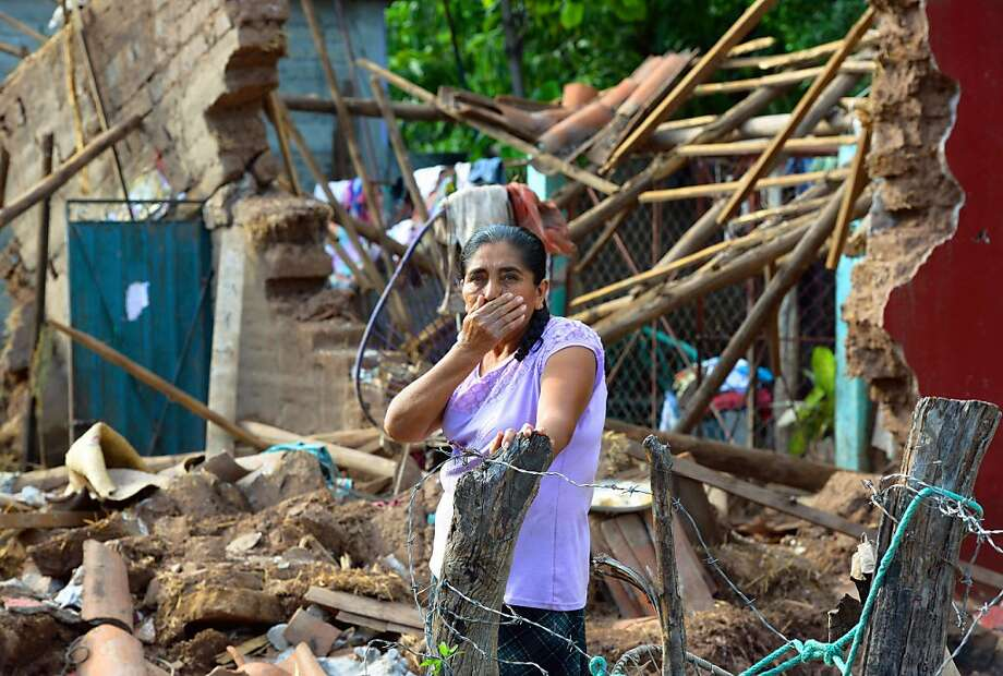 The damage done: A woman surveys what's left of her home in Coyuca de Catalan, Mexico, after twin storms struck Guerrero state 