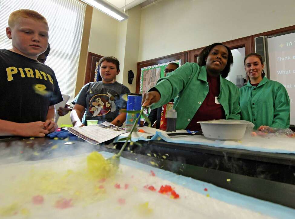 Biochemistry major Gabby Gregoire, second from right, shows Hackett Middle School students what happens when she puts a perfectly good flower into liquid nitrogen Wednesday, Sept. 25, 2013, during the Taste of College: College and Career Readiness Workshop at Hackett Middle School in Albany, N.Y. (Skip Dickstein / Times Union)