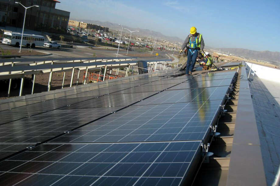 Workers install solar panels on the roof of a dining facility at Fort Bliss in El Paso. An E-N reader warns that rates will be even higher if San Antonio implements green energy sources. Photo: U.S. Army