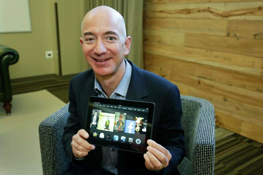 Jeff Bezos, CEO of Amazon.com, poses for a photo Tuesday, Sept. 24, 2013, with the 8.9-inch version of the new Amazon Kindle HDX tablet computer in Seattle. Amazon has refreshed its line-up of tablets with new devices, which are significantly faster and lighter than the previous generation. (AP Photo/Ted S. Warren) ORG XMIT: WATW101 Photo: Ted S. Warren / AP