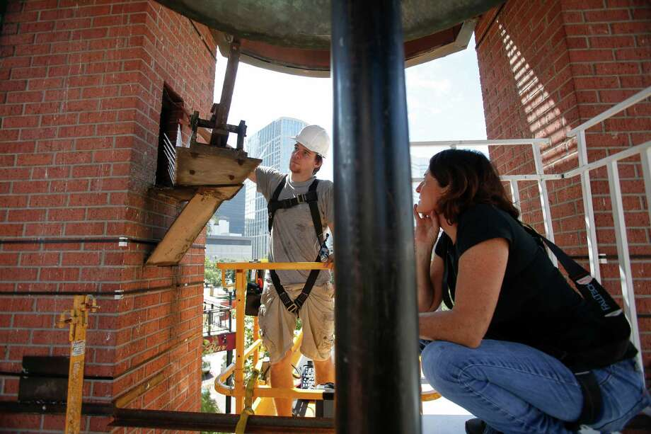 "Troy Stanley, left, helps Houston artist Jo Ann Fleischhauer install a public art work in and around the clock tower at Market Square  Sept. 23, 2013 in Houston. The work includes mirrors around the supports; a spiral staircase that will be used periodically by musicians for performances; and backlit images that become the backdrops for the clock faces. The work, called ""What Time is It?"" will be on display from Sept. 28 through March 29.