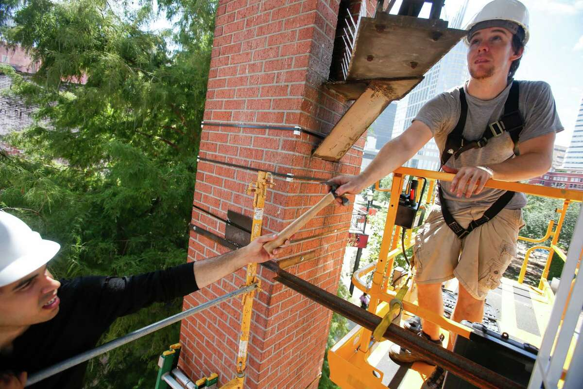 """Tommy Gregory, left, project manager with the Houston Arts Alliance, hands a hammer to Troy Stanley as they help Houston artist Jo Ann Fleischhauer install a public art work in and around the clock tower at Market Square Sept. 23, 2013 in Houston. The work includes mirrors around the supports; a spiral staircase that will be used periodically by musicians for performances; and backlit images that become the backdrops for the clock faces. The work, called """"What Time is It?"""" will be on display from Sept. 28 through March 29. (Eric Kayne/For the Chronicle)"""