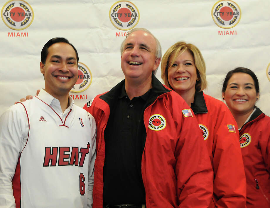 Miami-Dade Mayor Carlos A.Gimenez, second from left, persented San Antonio Mayor Julian Castro, left, with a Heat jersey, Wednesday, September 25, 2013, just before their work day with City Year began at Kelsey L.Pharr Elementary School, 2000 NW 46th St. On the right are Tere Blanca and Caroline Arroyo both with City Year.  The mayors joined over 50 volunteers, from City Year, for a beautification day at the school. Photo: MARICE COHN BAND, MIAMI HERALD STAFF / THE MIAMI HERALD
