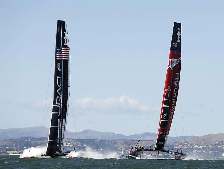 Oracle Team USA (left) hits the surf as and Emirates Team New Zealand pulls ahead at the start of Race 19 of the America's Cup Finals on Wednesday, September 25, 2013 in San Francisco, Calif. Photo: Beck Diefenbach, Special To The Chronicle