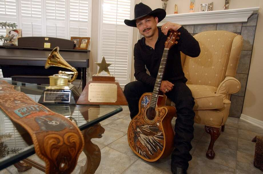 Tejano singer/musician Emilio Navaira poses for a portrait at his home in Von Ormy, Texas. Shown with Navaira are his two notables awards - his first Grammy award in 2002 and his first Tejano Music award from 1990. Photo: KIN MAN HUI, SAN ANTONIO EXPRESS-NEWS