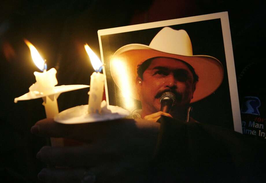 An Emilio Navaira fan holds a picture of the Tejano musician, during a prayer vigil and concert for Emilio Navaira at Guadalupe Plaza Park just east of downtown Tuesday, March 25, 2008. Navaira was injured and suffered trauma to the brain when in a tour bus accident on Interstate 610. Photo: Johnny Hanson, Houston Chronicle
