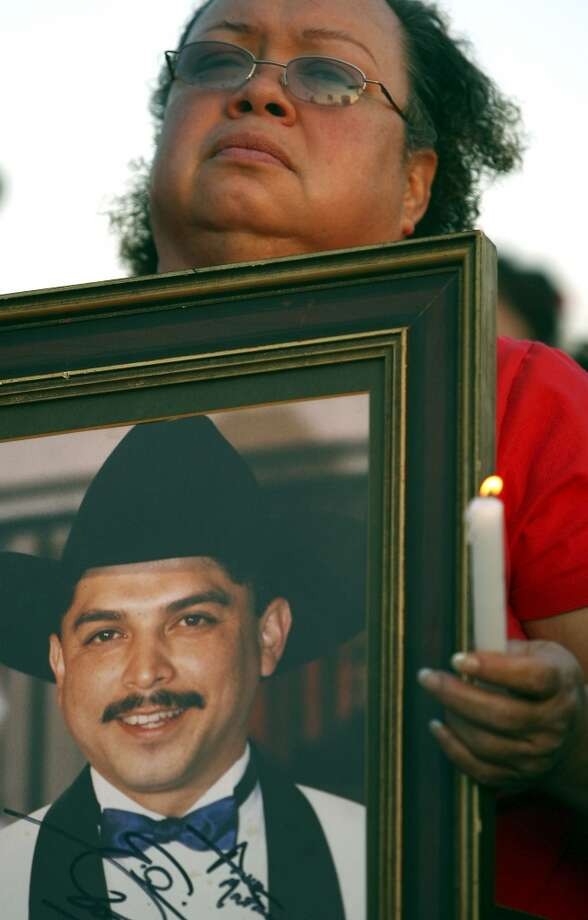 Emilio Navaira fan Anna Maria Martinez holds a photo of Navaira during a candle light vigil Monday March 24, 2008 in an Alamodome parking lot. Photo: EDWARD A. ORNELAS, SAN ANTONIO EXPRESS-NEWS