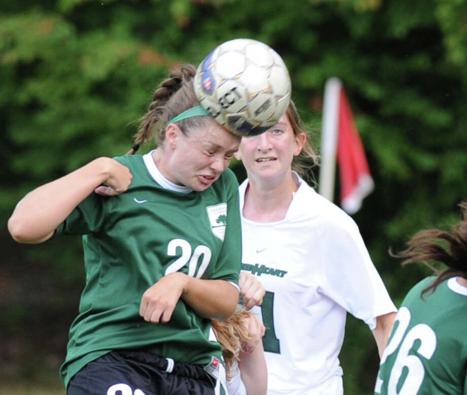 At left, Isabelle Dumoulin (# 20) of Greenwich Academy heads the ball during the girls high school soccer match between Greenwich Academy and Convent of the Sacred Heart at Greenwich Academy, Sept. 25, 2013. Photo: Bob Luckey / Greenwich Time
