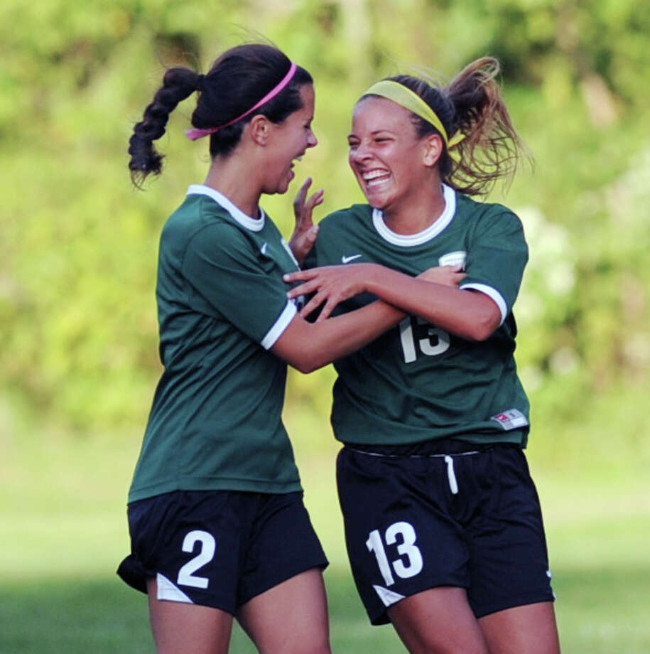 At left, Claudia Consuegra (# 2) of Greenwich Academy congratulates teammate, Emma Nossier (# 13), after Nossier scored a second half goal putting her team up, 2-0, during the girls high school soccer match between Greenwich Academy and Convent of the Sacred Heart at Greenwich Academy, Sept. 25, 2013. Photo: Bob Luckey / Greenwich Time