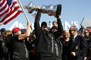Oracle Team USA skipper Jimmy Spithill hoists the America's Cup during the America's Cup Awards Ceremony in San Francisco, CA Wednesday September 25, 2013.