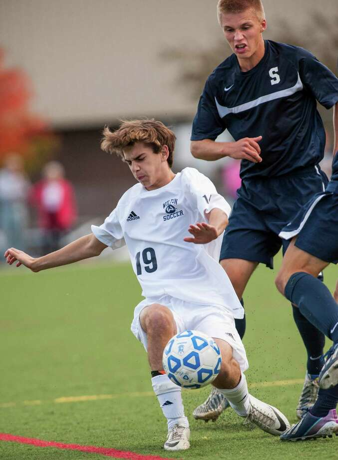 Wilton high school's Wyatt Dean and Staples high school's Andrew Puchala battle for the ball during a boys soccer game played at Wilton high school, Wilton CT on Wednesday September, 25th, 2013. Photo: Mark Conrad / Connecticut Post Freelance