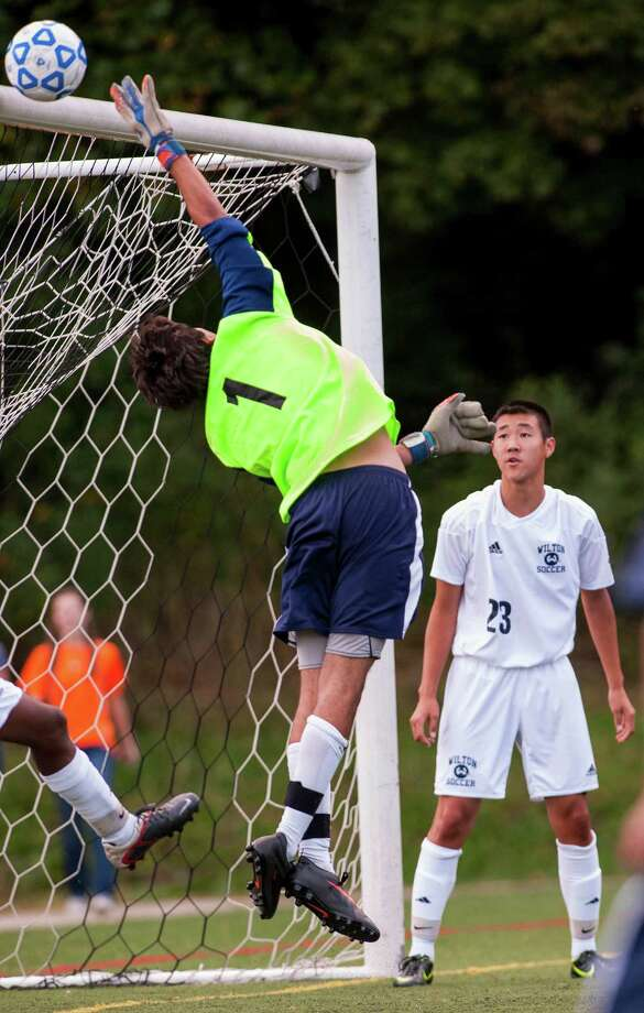 Wilton high school goalie William DeSantis jumps up to try and block a shot during a boys soccer game against Staples high school played at Wilton high school, Wilton CT on Wednesday September, 25th, 2013. Photo: Mark Conrad / Connecticut Post Freelance