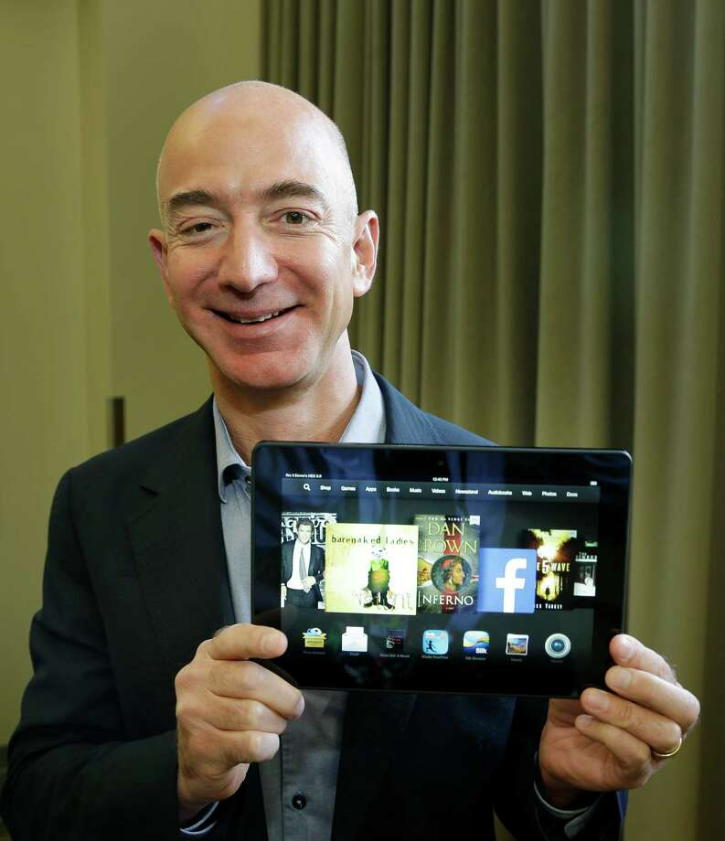 Jeff Bezos, CEO of Amazon.com, poses for a photo Tuesday, Sept. 24, 2013, with the 8.9-inch version of the new Amazon Kindle HDX tablet computer in Seattle. Amazon has refreshed its line-up of tablets with new devices, which are significantly faster and lighter than the previous generation. (AP Photo/Ted S. Warren) Photo: Ted S. Warren, STF / AP