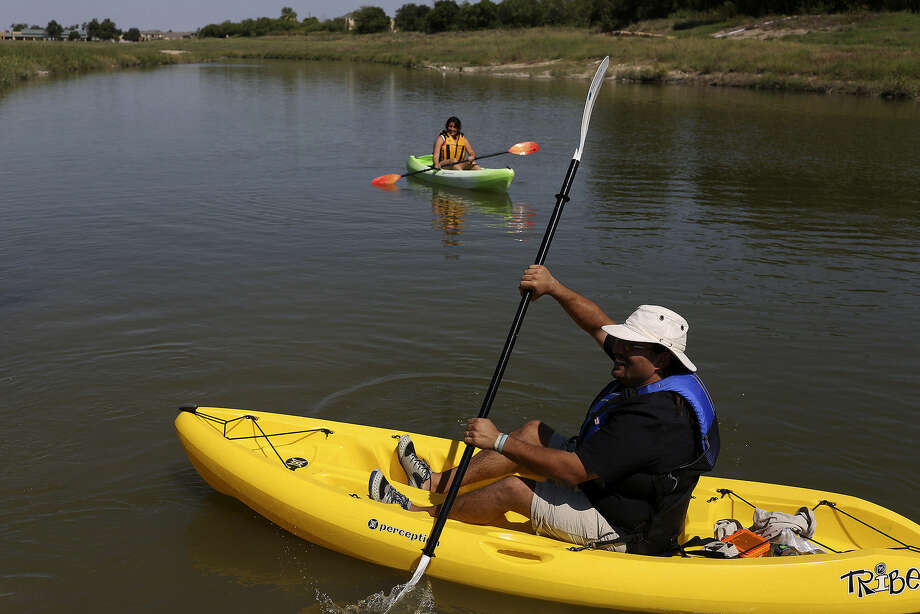 Federico Borroel, program manager for ChildSafe's Family Enrichment Adventure Therapy, and intern Mishel Lopez demonstrate kayaking on the Mission Reach. It's among several activities the program uses to help kids and family members. Photo: Lisa Krantz / San Antonio Express-News