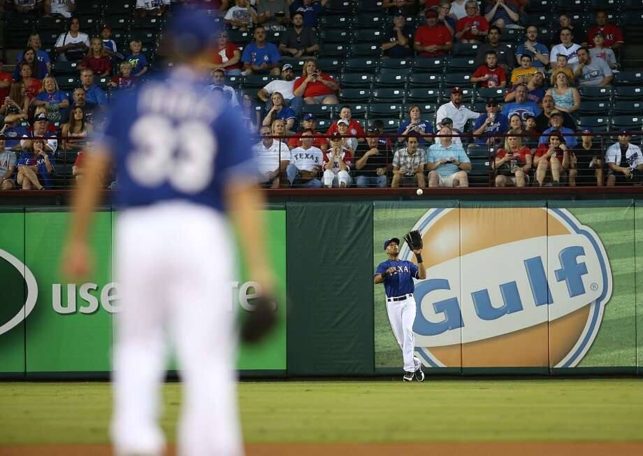 Martin Perez #33 of the Rangers looks on in the second inning as Alex Rios fields a fly ball hit by Chris Carter. Photo: Rick Yeatts, Getty Images