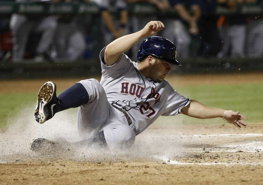 Jose Altuve (27) slides across home plate, scoring on a single by Chris Carter. Photo: Jim Cowsert, Associated Press