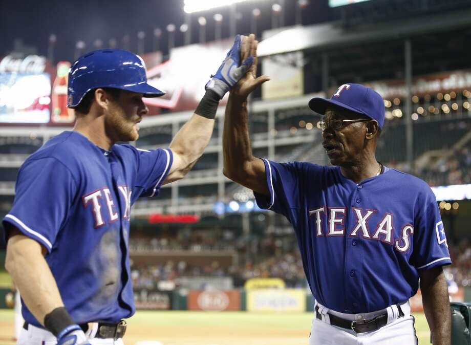Craig Gentry, left, is congratulated by manager Ron Washington (38) after scoring a run on a fielders choice single hit by Elvis Andrus. Photo: Jim Cowsert, Associated Press