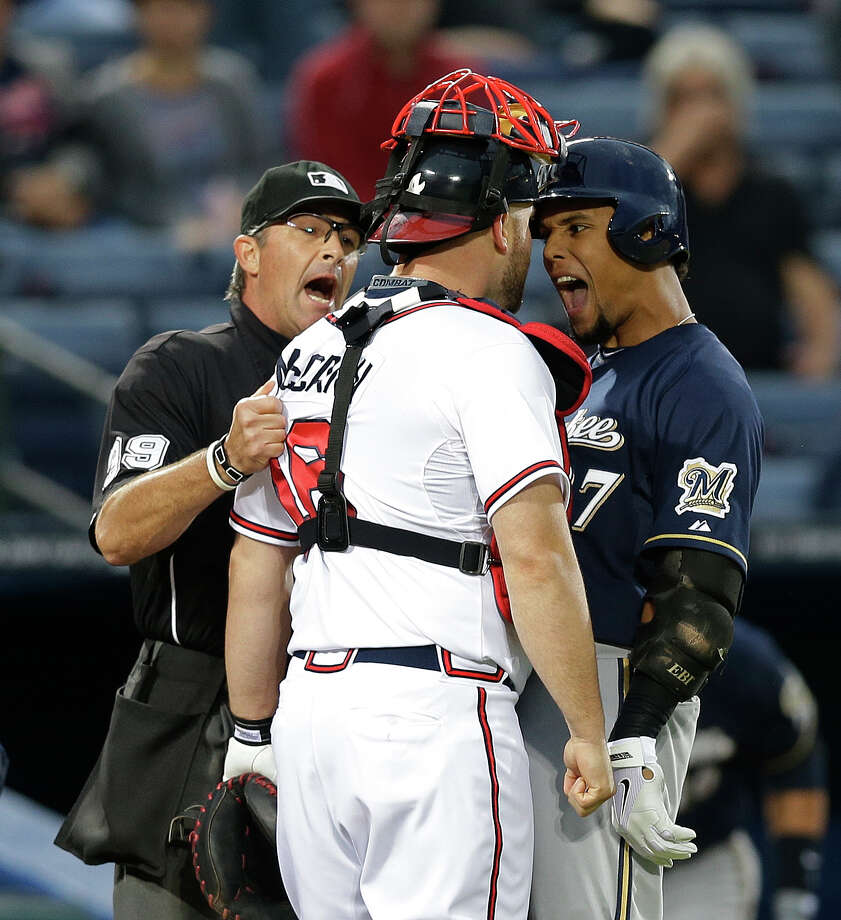 The Brewers' Carlos Gomez, right, and the Braves' Brian McCann face off in a confrontation that umpire Paul Nauert was unable to control. The exchange, precipitated by Gomez's antics following a homer, ignited a benches-clearing incident. Photo: John Bazemore, STF / AP