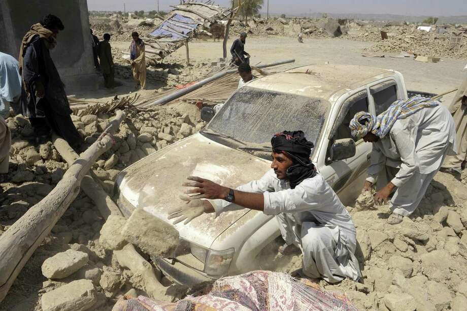 Pakistani survivors clear the debris of mud-walled houses destroyed in the earthquake-devastated district of Awaran on Wednesday. Photo: AFP/Getty Images