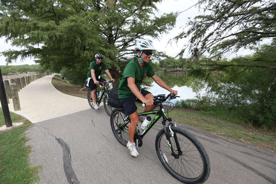 San Antonio Parks and Recreation Trail Stewards Marika Misangyi, right, and Charles Ford, ride around Southside Lions Pond, Thursday, Sept. 19, 2013. The stewards ride bikes along the trails from Sunday through Friday. They assist people walking and biking the trails. They also help maintain the trail clean. Photo: JERRY LARA, San Antonio Express-News / © 2013 San Antonio Express-News