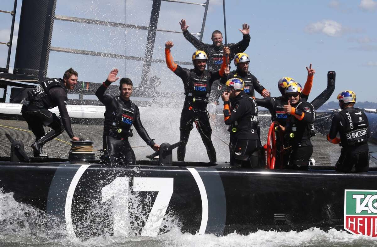 Oracle Team USA celebrates after winning Race 19 of the America's Cup Finals to take the America's Cup trophy on Wednesday, September 25, 2013 in San Francisco, Calif.