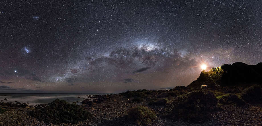 """Mark Gee, """"Guiding Light To The Stars""""Winner of Earth & Space Category (and Overall Winner of Astronomy Photographer of the Year 2013) """"Gee impressed the judges with the depth and clarity of his winning shot, depicting a star-riddled Milky Way  alongside the beam from a lighthouse on Cape Palliser, shining out towards the sea, the stars and the unknown. Competition judge and Royal Observatory Public Astronomer, Dr. Marek Kukula said: """"I love the tranquil combination of sea and sky in this beautiful image, along with the comforting human element of the cliff-top lighthouse. This view from the shores of New Zealand makes me think of the long voyages the Maori's ancestors made into unchartered oceans, guided by the stars. We're in a similar situation today, as we set out to explore the Universe"""". Photo: Mark Gee, Astronomy Photographer Of The Year 2013 Exhibition At The Royal Observatory Greenwich / Guiding Light To The Stars © Mark Gee 2013"""