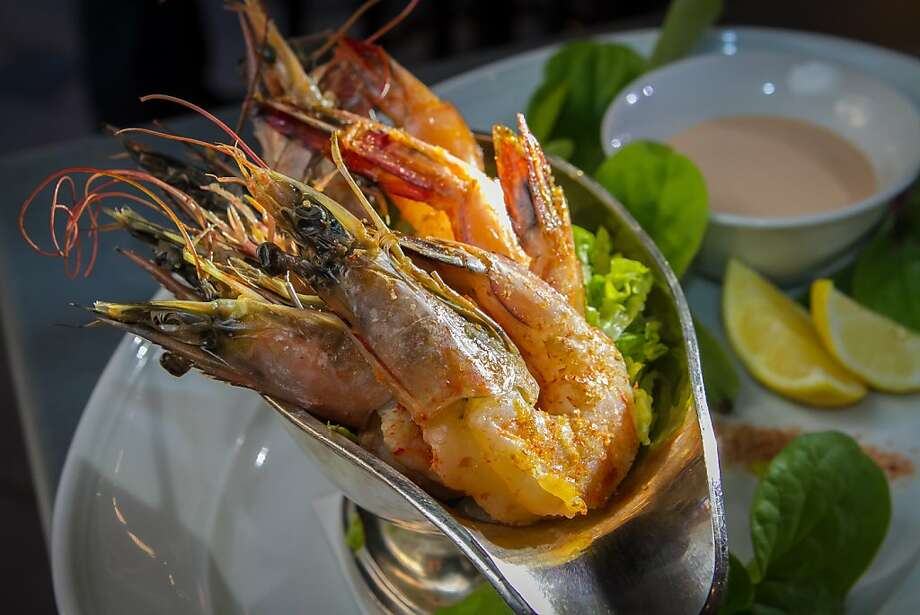 Boat of Prawns ($15) is an updated take on the shrimp cocktail, with five whole prawns accompanied by Marie Rose sauce and Malabar spinach. Photo: John Storey, Special To The Chronicle