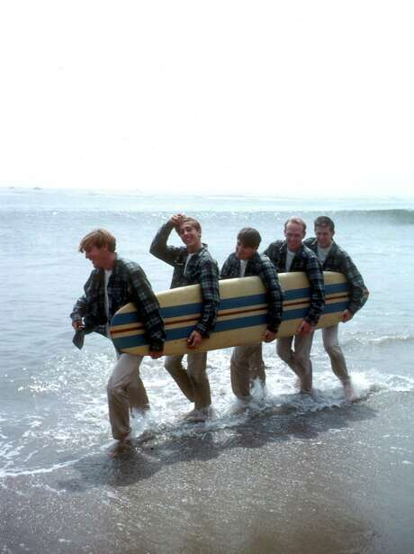 Rock and roll band 'The Beach Boys' walk along the beach holding a surfboard for a portrait session in August 1962 in Los Angeles, California. (L-R) Dennis Wilson, David Marks, Mike Love, Carl Wilson, Brian Wilson. Photo: Michael Ochs Archives, Stringer / Michael Ochs Archives