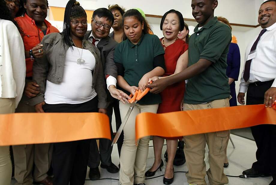 Westlake Middle School eighth-grader Leilani Sears cuts the ribbon on the SparkPoint program in Oakland. Mayor Jean Quan (center right) says SparkPoint, which provides a financial coach for parents, will help students as well. Photo: Michael Short, The Chronicle