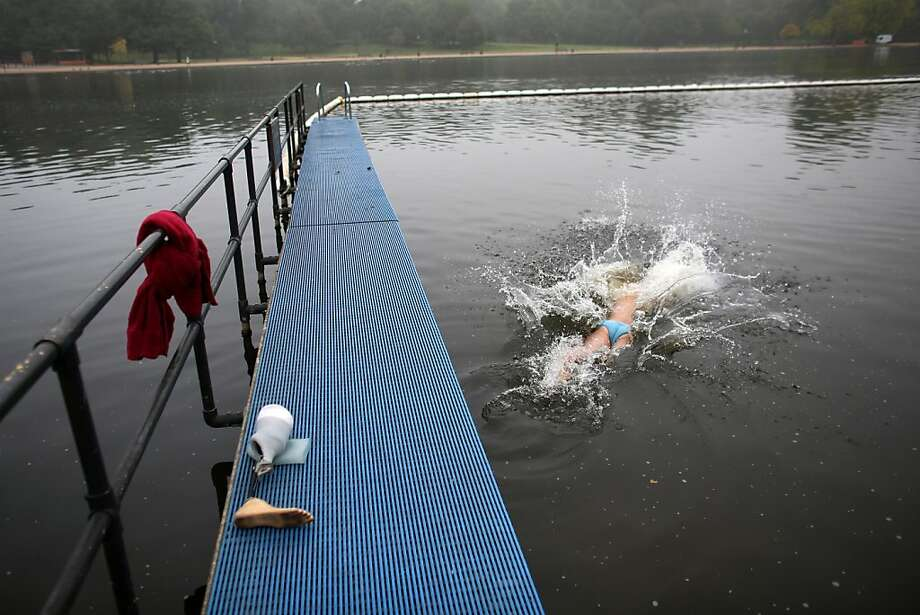 My left-behind foot: After shedding a prosthetic limb, an early-morning swimmer dives into Serpentine Lake in London's Hyde Park. Photo: Oli Scarff, Getty Images
