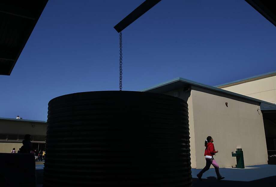 A student runs past a cistern built to store rainwater for gardens at Ulloa Elementary School in S.F. Photo: Leah Millis, The Chronicle