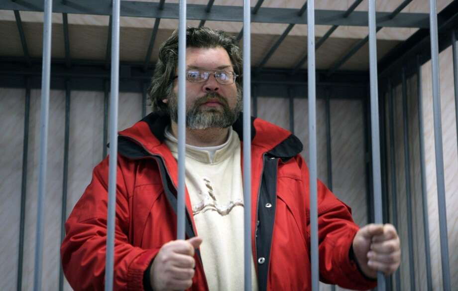 Greenpeace International expert Roman Dolgov stands in a defendant cage in a court in the northern Russian city of Murmansk. A Russian court ordered today two Greenpeace activists, Roman Dolgov and Greenpeace contracted freelance photographer Denis Sinyakov, both Russian citizens,  to be detained for two months over a protest on an Arctic oil platform, as the Netherlands called for the activists' immediate release and threatened legal action against Moscow. Photo: IGOR PODGORNY, AFP/Getty Images