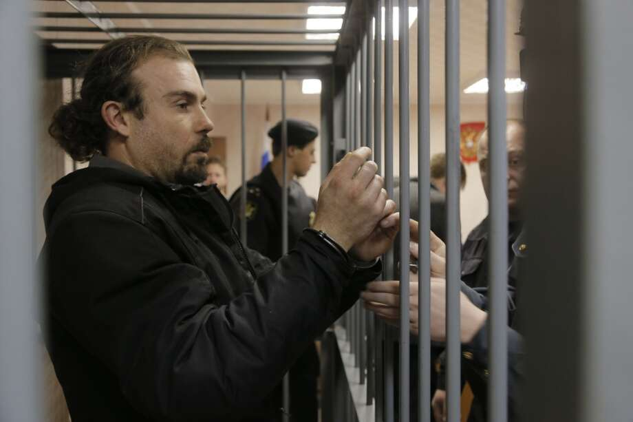 Police officers guard a cage with Greenpeace activist Pisanu Francesco Pierre (center) of France in a court room in Murmansk, Russia, Thursday, Sept. 26, 2013. Photo: Efrem Lukatsky, Associated Press