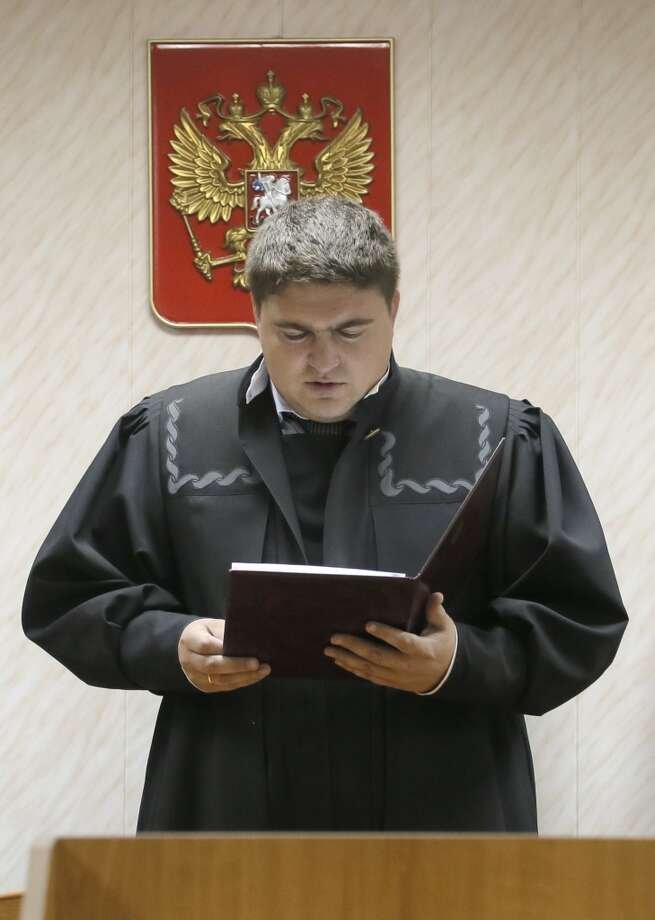 Dmitry Krivonosov, judge of Russian court, reads the verdict to Peter Willcox, the U.S. captain of the Greenpeace ship 'Arctic Sunrise',   in a court room in Murmansk, Russia, on Thursday, Sept. 26, 2013. Photo: Efrem Lukatsky, Associated Press