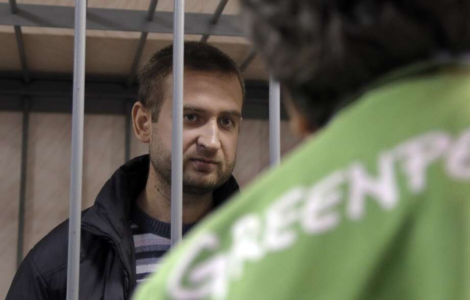 Greenpeace activist  Ruslan Yakushev of Ukraine behind bars speaks to a supporter in a court room in Murmansk, Russia, on Thursday, Sept. 26, 2013. Photo: Efrem Lukatsky, Associated Press