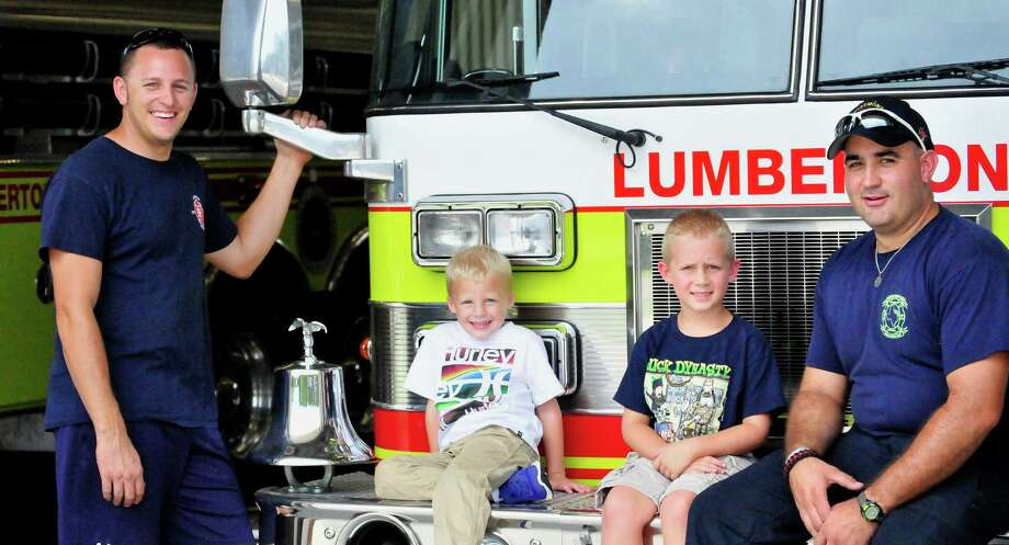 Mike and Ethan Birkby and Landon and Matt Kiser stopped by the Lumberton Fire & EMS station Sept. 18. Mike Birkby and Matt Kiser both volunteer for the station. Additional volunteer firefighters are needed as emergency responders face the city's growing pains. Photo: Cassie Smith