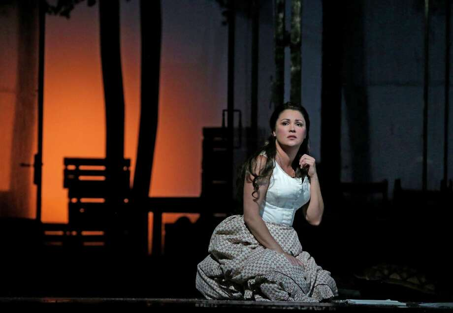 "In this Friday, Sept. 13, 2013 photo provided by the Metropolitan Opera, Anna Netrebko performs as Tatiana in Tchaikovsky's ""Eugene Onegin"" during a dress rehearsal at the Metropolitan Opera in New York. Netrebko opened the Met Opera season in 2011 as the lead in Gaetano Donizetti's ""Anna Bolena,"" and again in 2012 as the lead in the same composer's comedy, ""L'Elisir d'Amore."" When the Russian diva launches the Met season in ""Eugene Onegin"" on Sept. 23, 2013, it will mark her third consecutive opening night — a milestone no soprano has ever reached before in leading roles. (AP Photo/Metropolitan Opera, Ken Howard) ORG XMIT: NY116 Photo: Ken Howard / Metropolitan Opera"