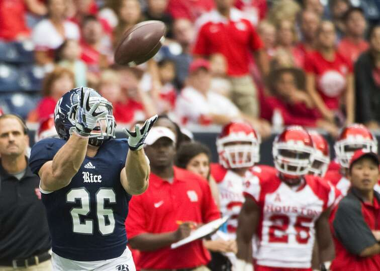 Rice running back Turner Petersen races down the sideline in front of the Houston bench as he catche