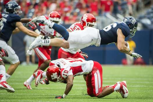 Rice running back Turner Petersen is upended by Houston defensive back Zachary McMillian. Photo: Smiley N. Pool, Houston Chronicle