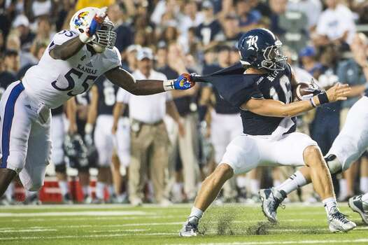 Rice quarterback Taylor McHargue slips away from the grasp of Kansas linebacker Michael Reynolds. Photo: Smiley N. Pool, Houston Chronicle