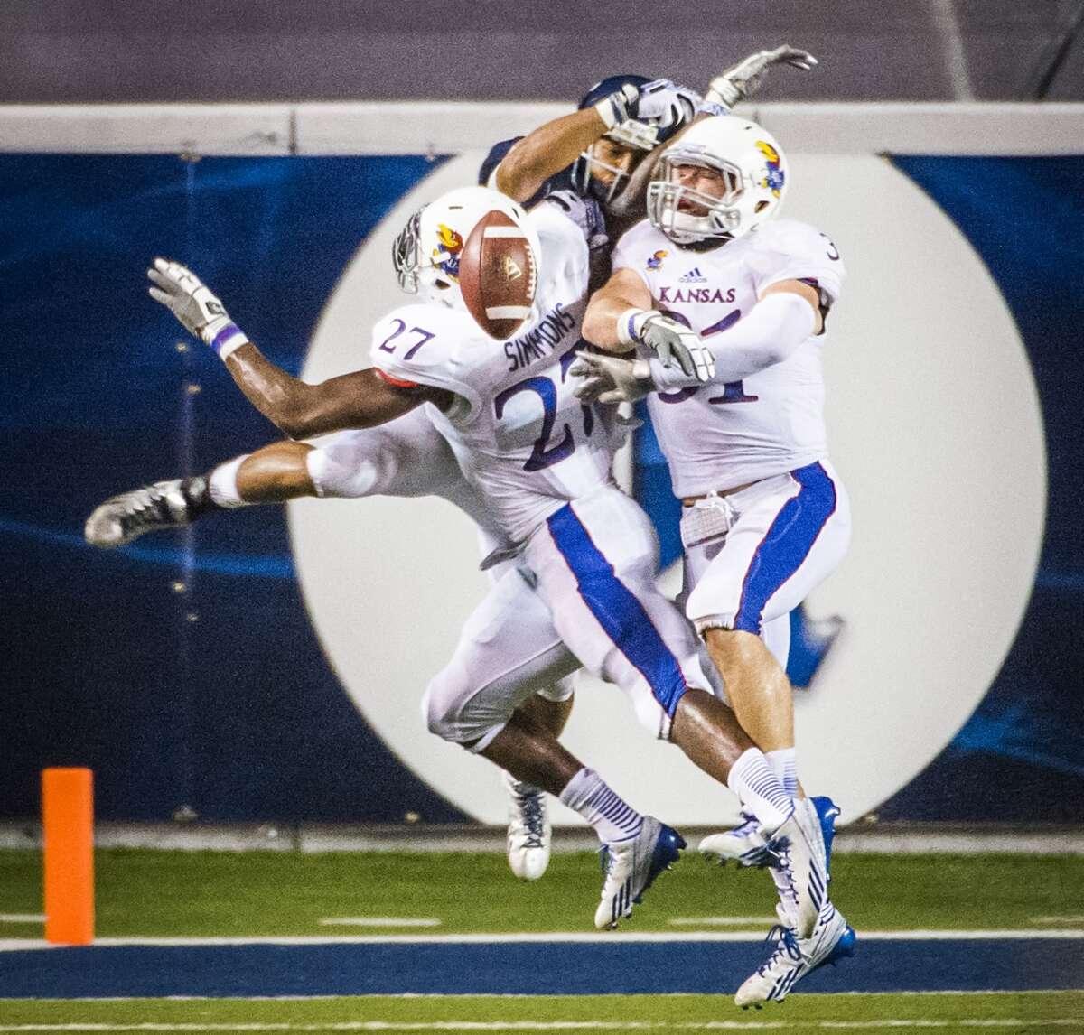 Kansas linebackers Victor Simmons (27) and Ben Heeney (31) break up a pass intended for Rice running back Darik Dillard.